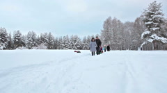 People walk along snow pathway with tube. Ski resort with tubing slope forest Stock Footage