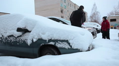 Building parking area with snow covered cars and family brushing own vehicle Stock Footage