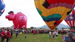 Crowds enjoying a morning at a hot air balloon festival Stock Footage