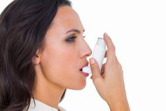 Asthmatic brunette using her inhaler Stock Photos