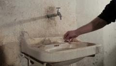 Guy approaches a dirty sink, leaves used syringe and washed hands and face. Stock Footage