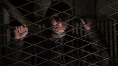 Kidnapped girl in the basement shaking door grilles, trying to get out (escape). Stock Footage