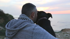 Man and dog watch the sunset Stock Footage
