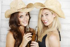 two friends in beachwear and hats - stock photo