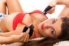 Hot brunette with handcuffs Stock Photos