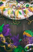 Stock Photo of mardi gras: king cake with party mask, hat and tiara