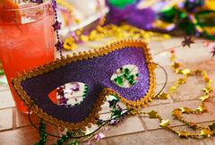 mardi gras: party mask sits against tropical hurricane cocktail - stock photo
