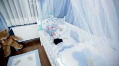 Babys room, baby nursery, babys bedroom.baby is lying in his crib - dolly shot Stock Footage
