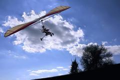 flying motorized hang glider - stock photo