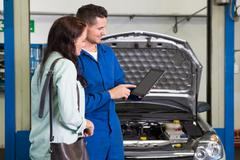 Mechanic showing customer the problem with car Stock Photos