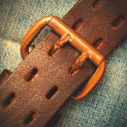 clasped leather belt on jeans background - stock photo