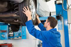Mechanic adjusting the tire wheel - stock photo