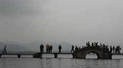 Tourists and stone bridge on west lake on a overcast day Stock Footage