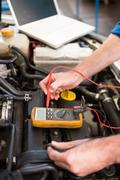 Stock Photo of Mechanic using diagnostic tool on engine