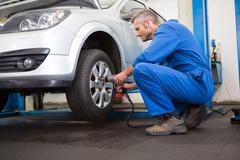 Stock Photo of Mechanic adjusting the tire wheel
