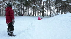 Boy stained snow looking at girl tubing downhill on snow, winter forest Stock Footage
