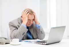 Upset older businessman with laptop and telephone Stock Photos