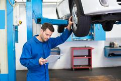 Mechanic looking at car tires Stock Photos