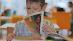 Little boy school-age sitting at the table with a big book Stock Footage