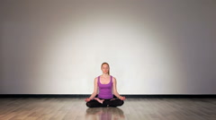 Female in magenta t-shirt meditating in lotus position Stock Footage