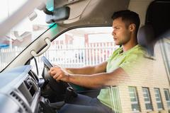Stock Photo of Serious delivery man driving his van