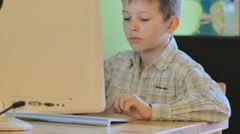 School age boy sitting at a desk and using a computer Stock Footage