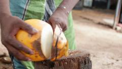 Man cuts king coconut for drink with sharp knife Stock Footage