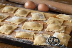 raw agnolotti pasta on cutting board - stock photo