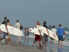 Surfers heading to ocean on Cocoa Beach Stock Footage