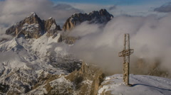 Cross on top of Sella peak, Sasso Lungo covered in clouds, winter 4K Stock Footage