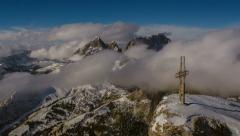 Cross on top of Sella peak, Sasso Lungo covered in clouds, Campitello ski resort Stock Footage