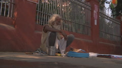 Old man sitting on the street at Delhi circa 2014 in India Stock Footage