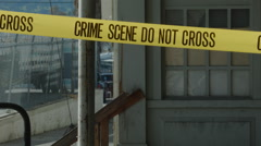 CRIME SCENE TAPE STRETCHED ACROSS FRAME. INDUSTRIAL BACKGROUND. Stock Footage
