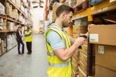Warehouse worker scanning barcode on box - stock photo