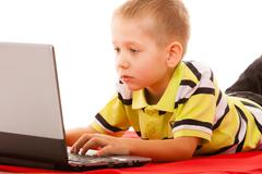 education, technology internet - little boy with laptop - stock photo
