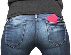 girl's bum with red paper heart in her jeans pocket - stock photo