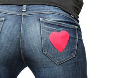 girl's bum with red paper heart on her jeans pocket - stock photo