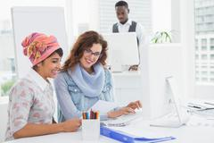 Casual coworkers smiling and suing computer Stock Photos