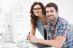 Smiling designer colleagues using digitizer together - stock photo