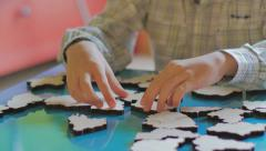 Younger boys collect puzzle in the form of map elements Stock Footage