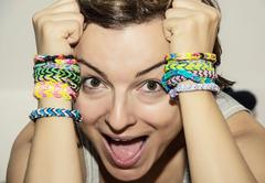 crazy young woman with colorful rubber bracelets on her hands - stock photo