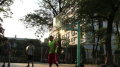 College students playing basketball in playground Stock Footage