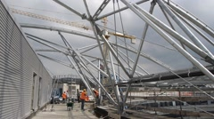 Workers constructing metal beam roof Stock Footage