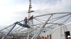 Wide shot of workers constructing metal beam roof Stock Footage