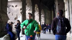 Tourists inside Colosseum in Rome. FPV of the going tourist. - stock footage