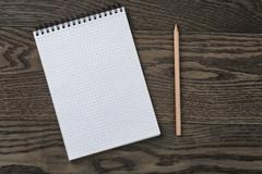 Blank notepad and pencil on the wooden table Stock Photos