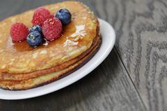 Stock Photo of pancakes with berries and maple syrup, on wooden table
