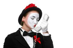 Woman in the image mime holding a handset - stock photo