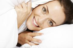 woman under bed sheets - stock photo