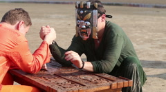 Man wrestling with man in mask on wooden fretted table on beach Stock Footage